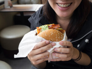 person with braces eating a bacon burger